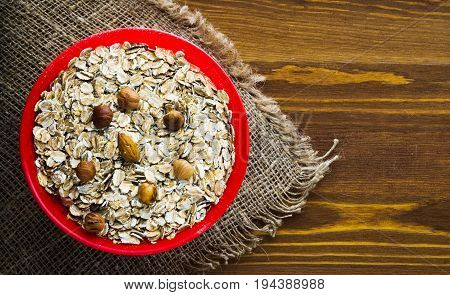 Oatmeal With Nuts (hazelnuts,  Almonds). Oatmeal On A Wooden Table. Oatmeal Top View. Healthy Food .