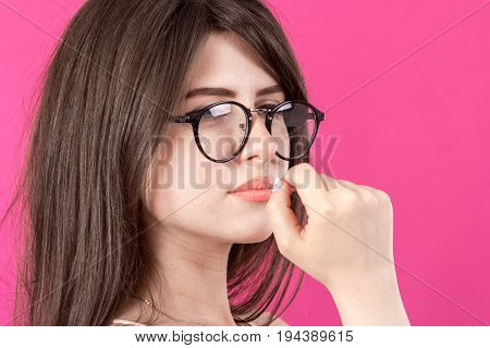 portrait of the beautiful young smiling woman with glasses on pink background