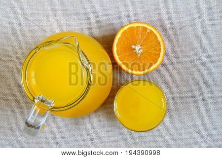 Jug and glass of orange juice and ripe oranges from above top view on burlap sackcloth background