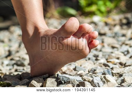 Close-up of bare foot walking on stones outdoors activity