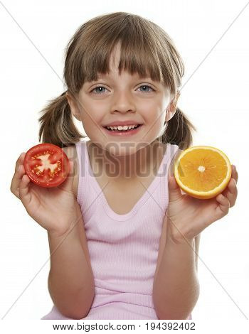 little girl holding a half tomato and a half orange