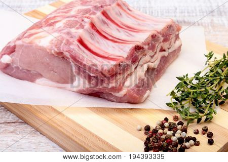 Raw pork chops, spices and rosemary on cutting board. Ready for cooking