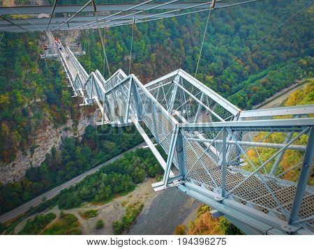 Metal bridge stair staircase above river. Metal architecture. Bangee jumping SkyPark Sochi adrenaline places for tourists. Best sightseeing holiday vacation tours.