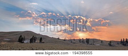 Pink and orange Sunbeams and sunrays through sunset clouds in the Hayden Valley in Yellowstone National Park in Wyoming USA poster