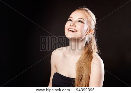 Close-up portrait of beautiful model with long blond hair on black background