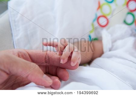 A new father holds his newborn infant baby's hand for the first time. Parent holding newborns hand. Hand in hand. Parenthood. Motherhood. Fatherhood. Family.