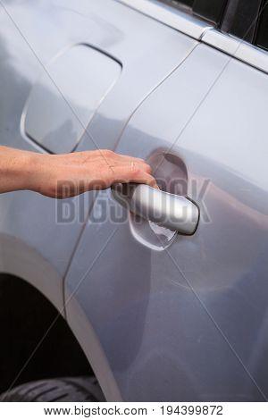 Human hand holding silver car door handle opening doors going into vehicle.