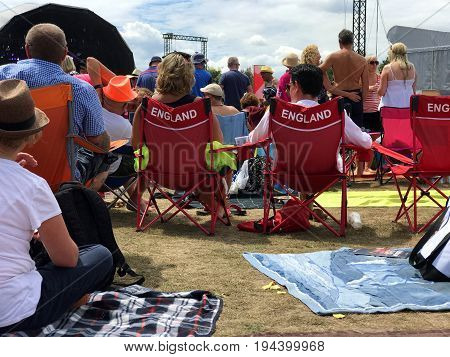 SOUTHAMPTON UK - July 8 2017: Lets Rock Southampton 80s music festival in Southampton UK. People sitting in red England chair listening to the festival music.