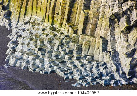 Big basalt rocks covered with yellow and blue moss on the beach