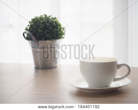 wood table with white coffee cup of latte coffee small tree garden on pot and blurry white drape texture background view from front wood table.