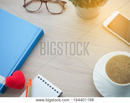 wood office table with free space frame for text and black hot coffee blank screen on cell phone flower on pot red heart shape sign modern eyeglasses. view from top office table.