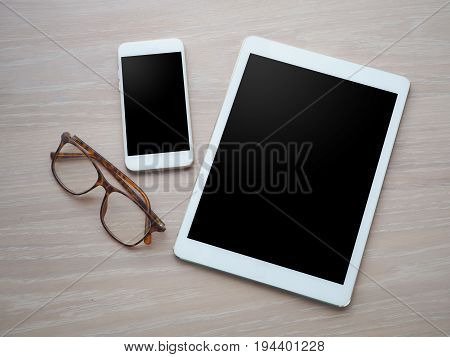 wood office table with blank screen for text on tablet smart phone cell phone and modern eyeglasses. view from top wood table.