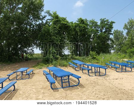 Blue picnic benches along sand dunes at Silver Beach County Park in St. Joseph, Michigan