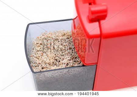 Red pencil sharpener with pencil trash on white background