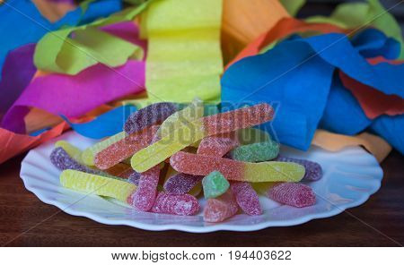 Sour worm confectionery sweet treats covered in sugar on white plate with party streamers