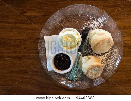 Hot scone cakes on glass plate with fresh cream and jam on wooden table