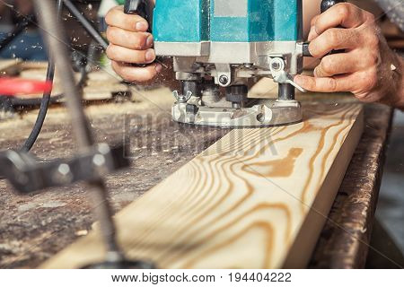 A close-up of a wooden board with a green milling machine on a wooden table