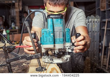 A young brunette man carpenter in green goggles equals a wooden plank with a milling machine in the workshop
