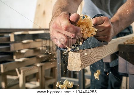 A close-up as a Young man is treating a wooden bar with a black jack plane in the workshop in the background a lot of wooden boards