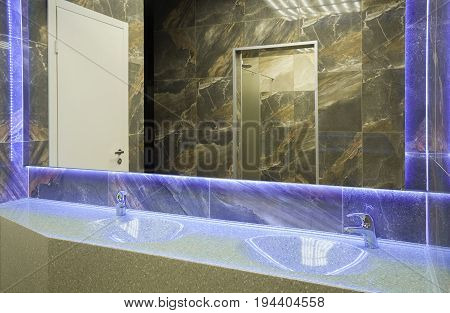 Large washbasin with panoramic mirror in the bathroom with marble finish