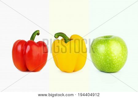 Fresh big red and yellow peppers and big green apple on white isolated background in the middle in one row