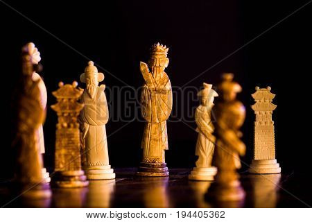 Pieces of chess made in ivory on a dark background.