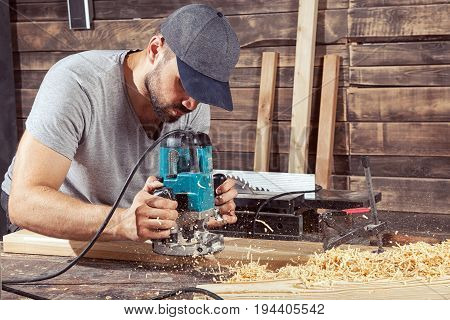 A young man in a gray cap and a gray T-shirt carpenter builder holds a milling machine in the hand and equips the edges of the wooden board in the workshop wooden sawdust flies to the sides