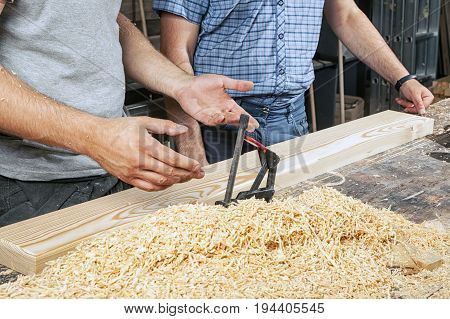 Close-up as two men in a T-shirt and a checkered shirt stand near a wooden table and discuss how to process a wooden board with a milling machine around a lot of wooden sawdust
