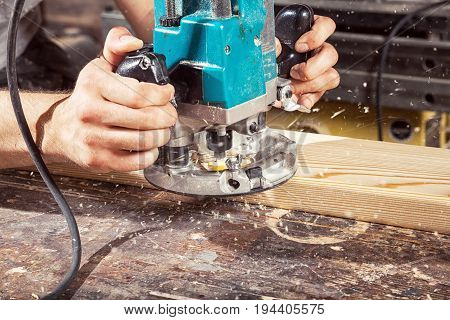 Close-up of how a modern green milling machine works on wood on a wooden table background