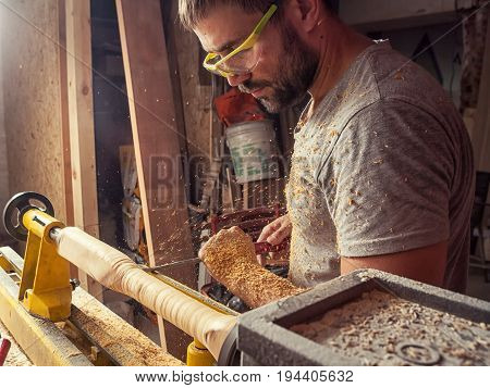 A young man with dark hair and goggles holds a stalker in his hands and processes a wooden product on a lathe in the workshop