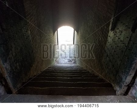 very old stairs and bright light at the end of the stairs