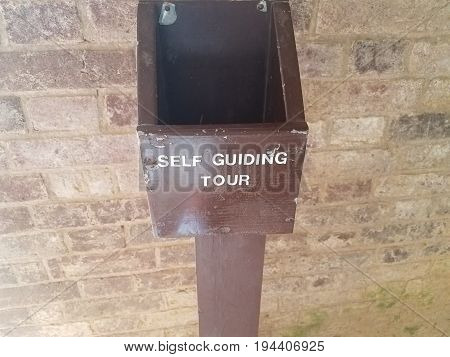 brown wood box that says self guided tour and brick wall