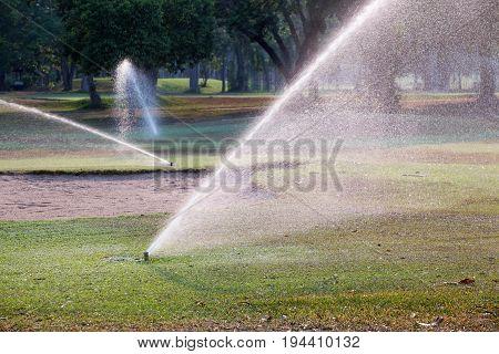 Sprinkler watering grass in golf course .