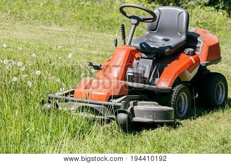 Red Lawn Mower On Green Grass Lawn In Sunny Day