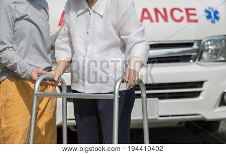 senior woman using a walker with caregiver to take ambulance .
