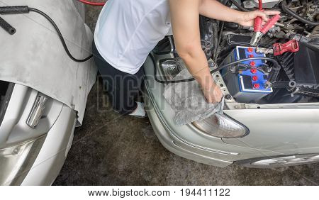 Woman  trying to jump start a car at parking lot .