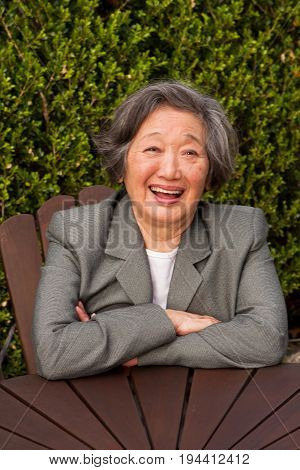 Portrait of happy Asian woman smiling outside.