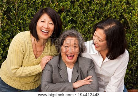 Happy mature Asian mother and her adult daughters.