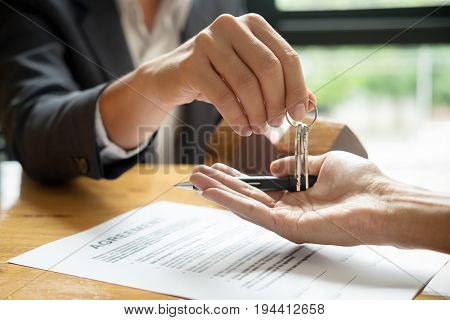 Real Estate Agent Holding House Key To His Client After Signing Contract,concept For Real Estate, Mo