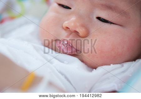 Focus at Asian newborn baby girl is playing with her saliva when she is sleeping on the bed.