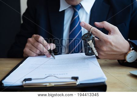 Successful Businessman Offering A Car Key With Contract.rental Agreement For A Car With Contract.car