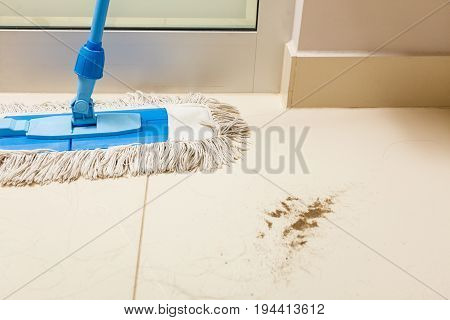 Taking care of household equipment concept. Dirty floor with sand and cleaning mop standing next to it