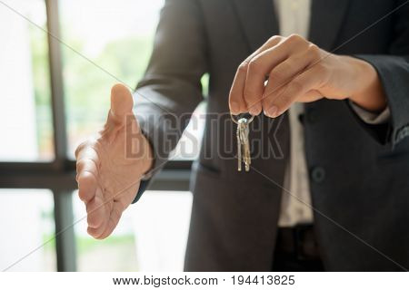 Real Estate Agent Shaking Hands And Holding House Key To His Client After Signing Contract,concept F