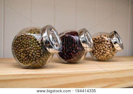 Many nuts are put in jars on the shelves.