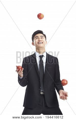 young asian business man wearing suit and tie juggling three apples isolated on white background.