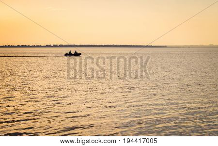 Two fishermen sail along the Ukrainian estuary onto a motor boat leaving a trail behind them