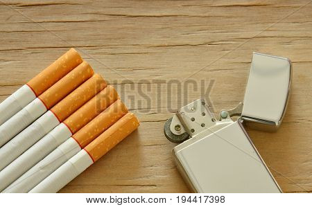 silver lighter and cigarette on wooden board