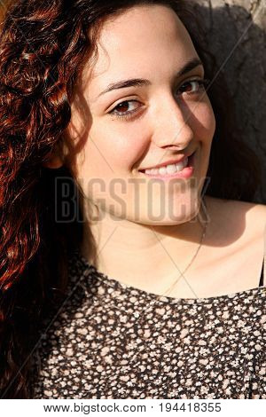 Curly, beautiful young happy woman. Portrait of a curly girl smiling. She has beautiful brown curly hair. Brown eyes.