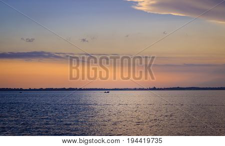 Fishing boat sails along the estuary beautiful evening bright sky in different colors wonders of Ukrainian nature