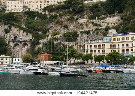 Row of small houses along seaside on the slope of hills and boats parked.